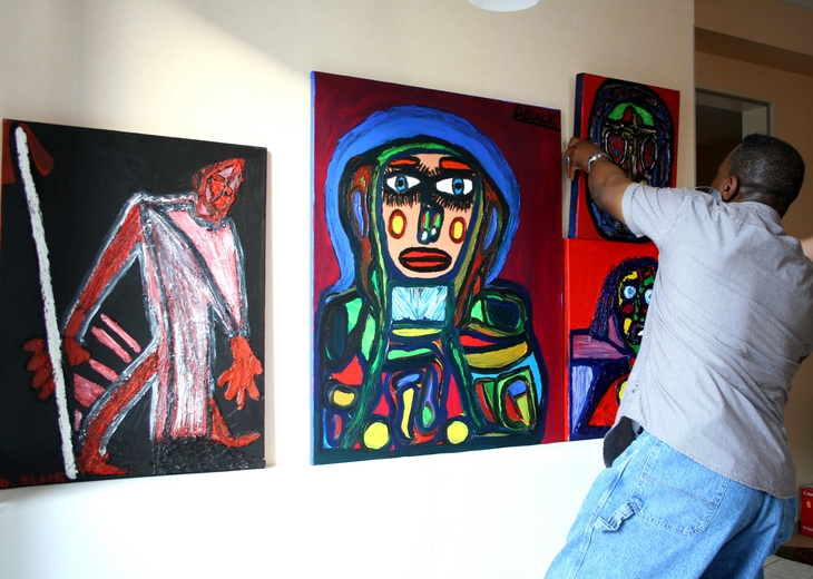 The artist Darrell Black in his studio hanging paintings