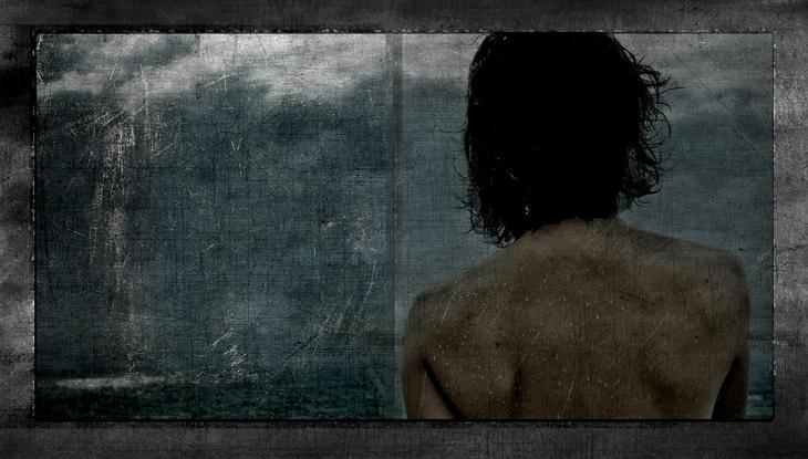 Elle regard l'ocean sur la terrasse de l'hotel